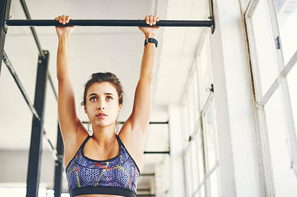 Low angle view of young female doing chin-ups stock photo