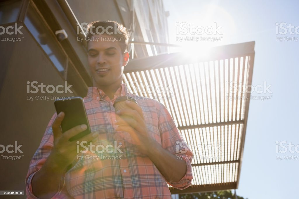 Low angle view of young man using mobile phone stock photo