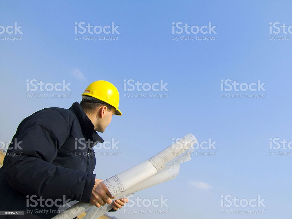 Low angled view of an engineer in a hard hat holding plans stock photo