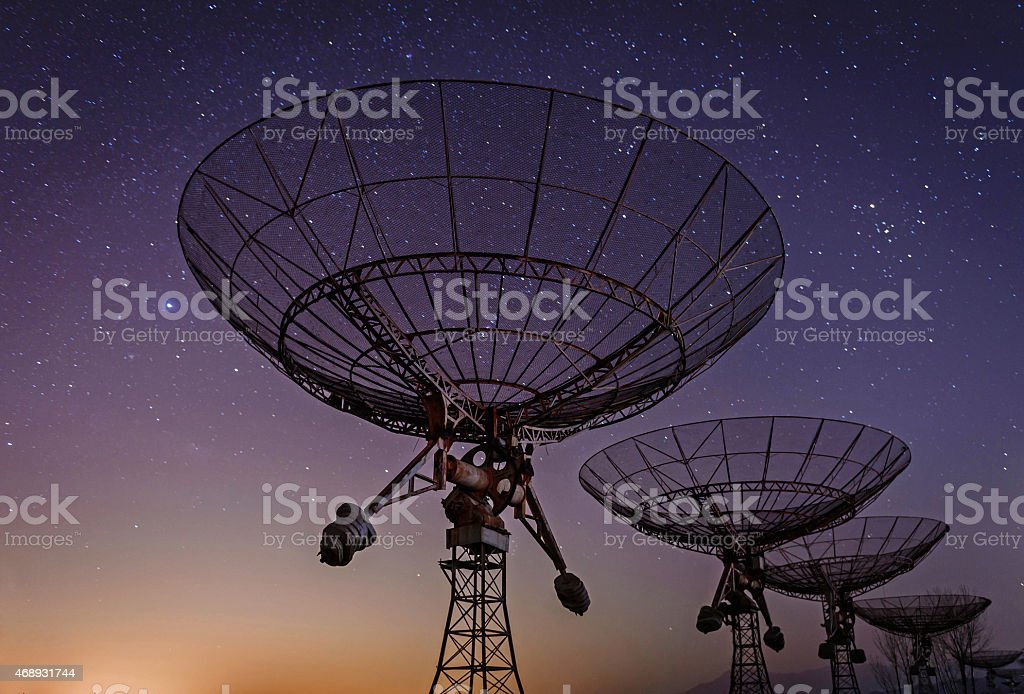 Low angled view of radio telescopes with Milky Way in sky stock photo