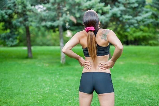 unteren rücken schmerzen während sports activity - unterer rücken tattoos stock-fotos und bilder