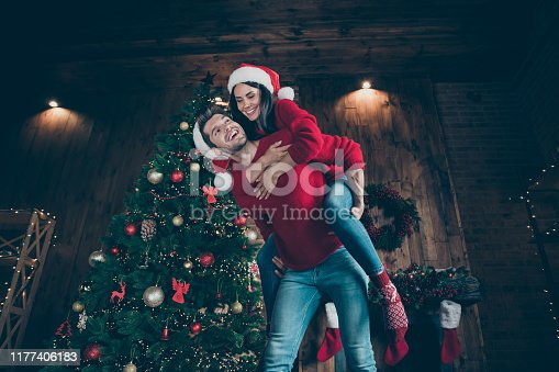 Low below angle view of nice attractive lovely funky cheerful cheery best close friends, spending leisure having fun amusement in decorated lights loft industrial brick wood style interior indoors