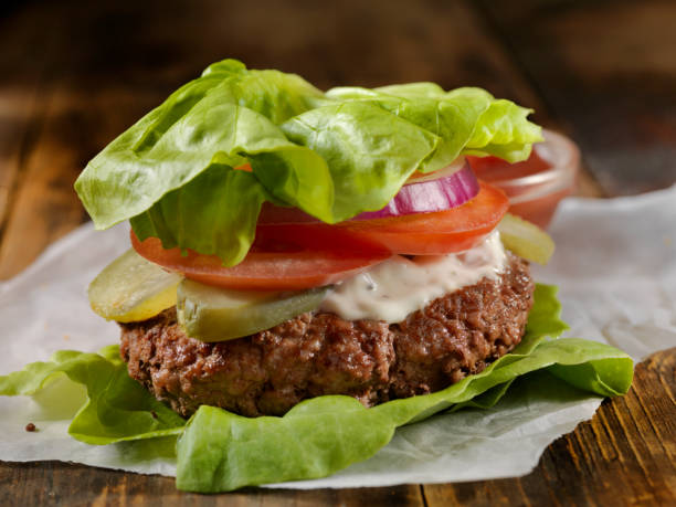 Low Carb - Lettuce Wrap Burger Low Carbohydrate - Lettuce Wrap Burger with Tomato, Onion and Mayo bacon cheeseburger stock pictures, royalty-free photos & images