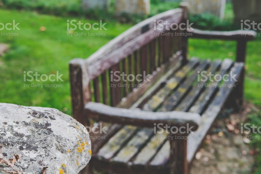Low contrast, shallow focus view of the lip of an ancient stonework vault, shown with an out of focus wooden bench seen in the background. stock photo