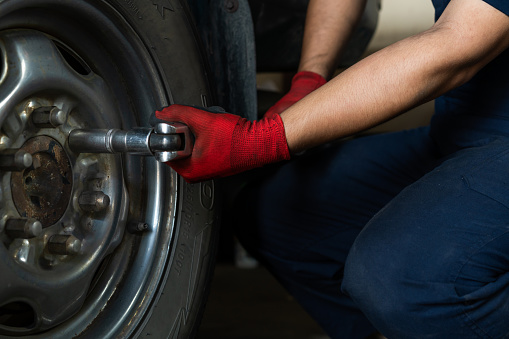Hands of technician using a torque wrench to remove car wheel bolts - Low view of a auto repair mechanic operating hand tools to secure wheel and tire in a garage
