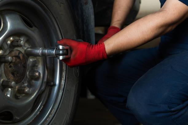 niedrige down-ansicht eines mechanikers mit einem steckschlüssel, um radschrauben aus einem fahrzeug zu entfernen - pickup trucks stock-fotos und bilder