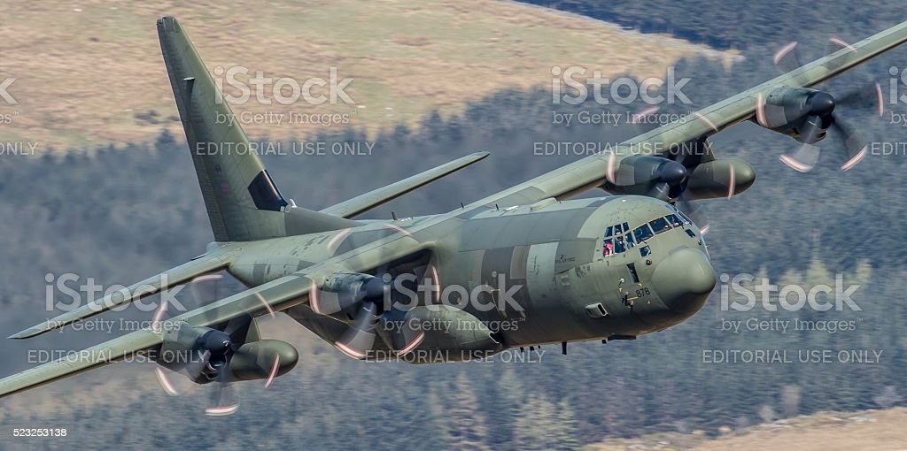 Low flying C-130 Hercules military transport aircraft stock photo