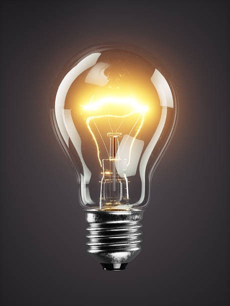 Low glowing electric bulb lamp on dark background stock photo