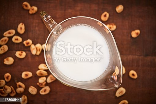 Shot of a jug of milk surrounded by nuts on a table