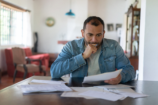 Latin American low income man checking his home finances and looking worried while looking at the utility bills - lifestyle concepts