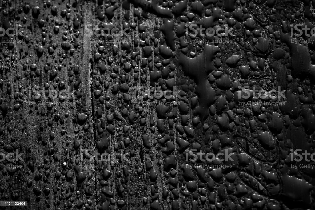 Low key black and white photo of raindrops on park bench stock photo
