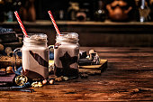 Low key chocolate smoothies on a table in a rustic kitchen