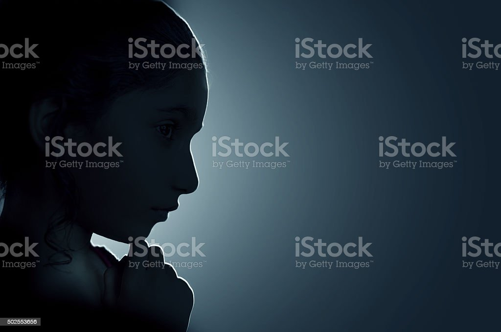 Low key girl child hand on chin portrait stock photo