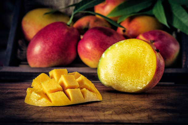 Low key image close-up of sliced ripe mangoes in rustic kitchen stock photo