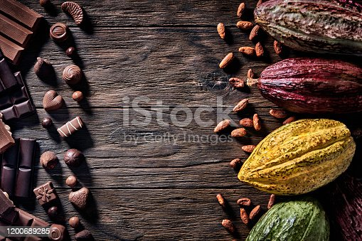 Low key image of assorted chocolate and cacao fruits in old fashioned style on a wooden rustic table and copy space in frame