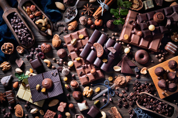 Low key image of assorted chocolate and dried cocoa beans in old fashioned style on a wooden rustic table stock photo
