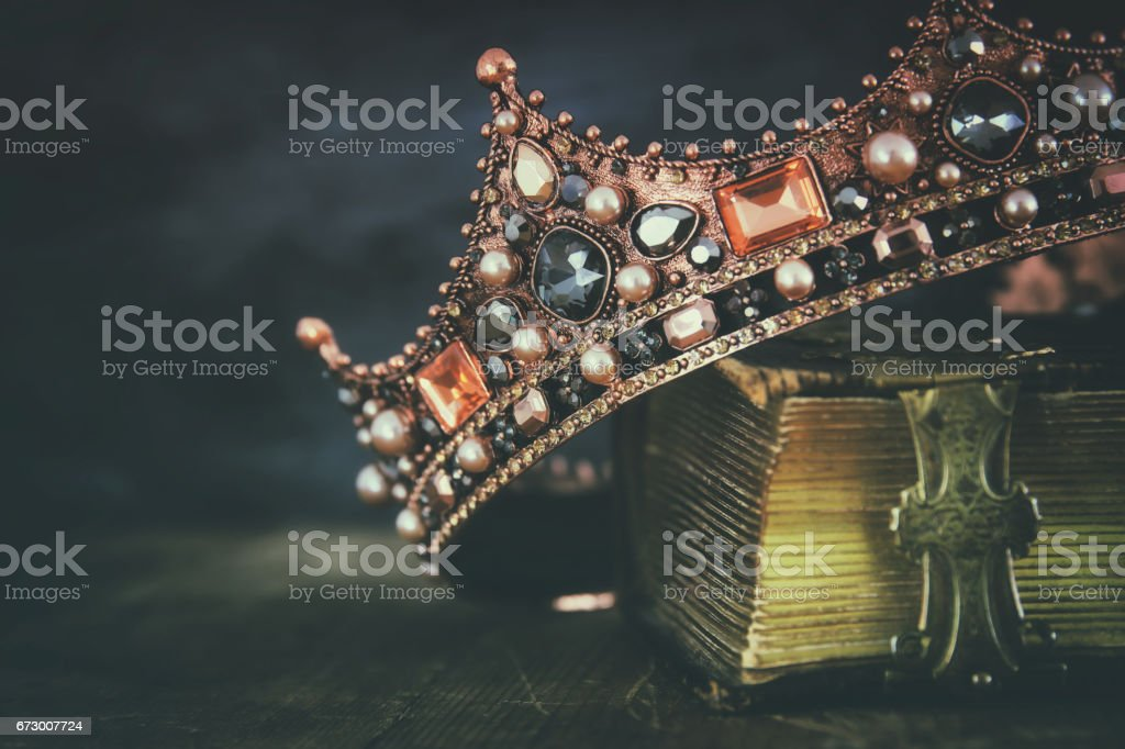 low key image of beautiful queen/king crown on old book low key image of beautiful queen/king crown on old book. vintage filtered. fantasy medieval period Ancient Stock Photo