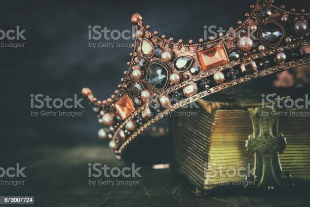 low key image of beautiful queen/king crown on old book. vintage filtered. fantasy medieval period