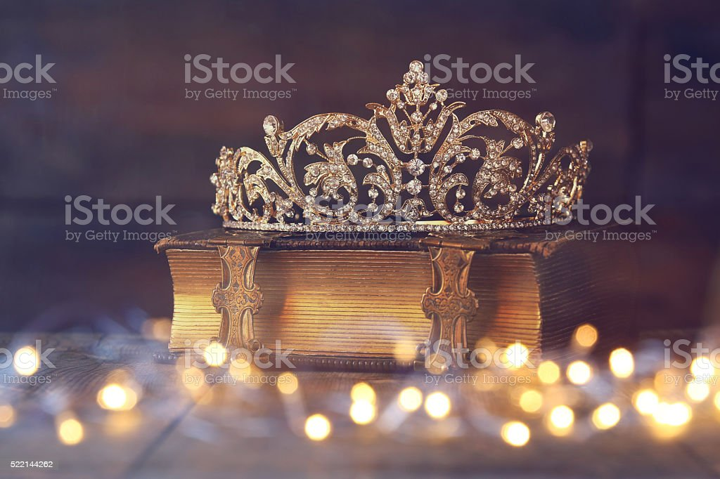 low key image of decorative crown on old book stock photo