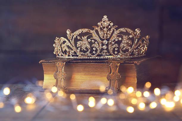 Bajo la imagen de corona de decoración en libro viejo - foto de stock
