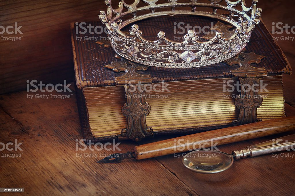 low key image of diamond queen crown on old book stock photo