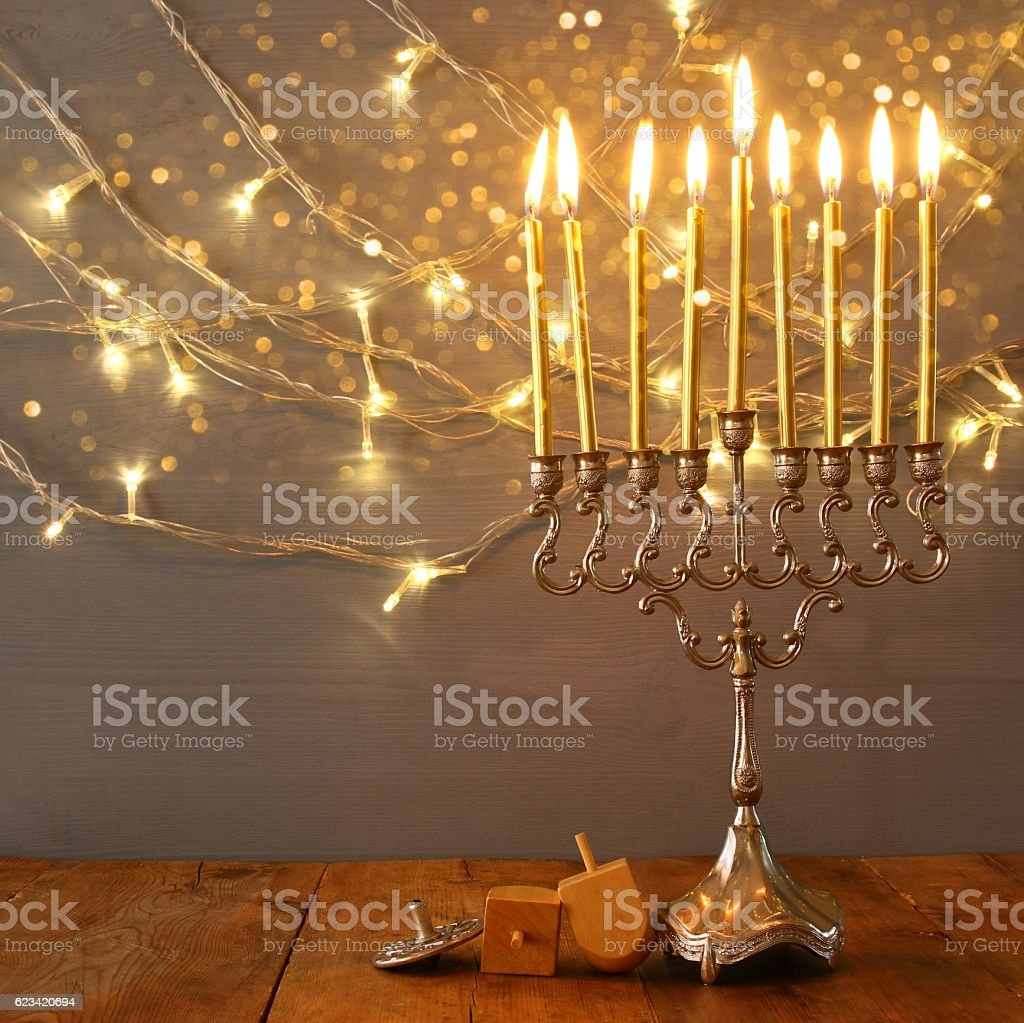 Low key Image of jewish holiday Hanukkah with menorah and wooden...