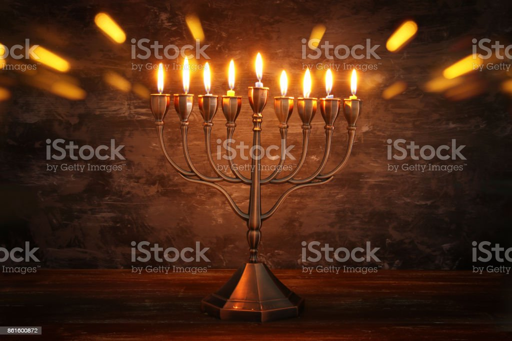 Low key image of jewish holiday Hanukkah background with menorah and...