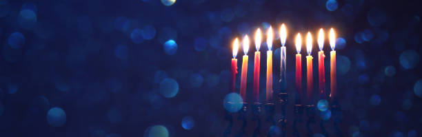 low key image of jewish holiday Hanukkah background with menorah (traditional candelabra) stock photo