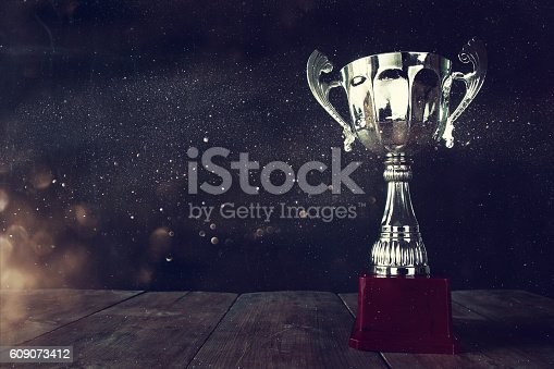 istock low key image of trophy over wooden table 609073412