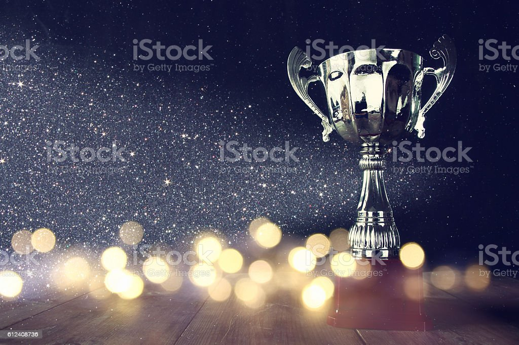 low key image of trophy over wooden table low key image of trophy over wooden table and dark background, with abstract shiny lights Achievement Stock Photo