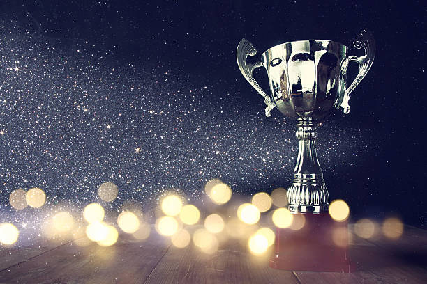 low key image of trophy over wooden table - trophy award stock photos and pictures