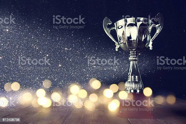 Low Key Image Of Trophy Over Wooden Table Stock Photo - Download Image Now