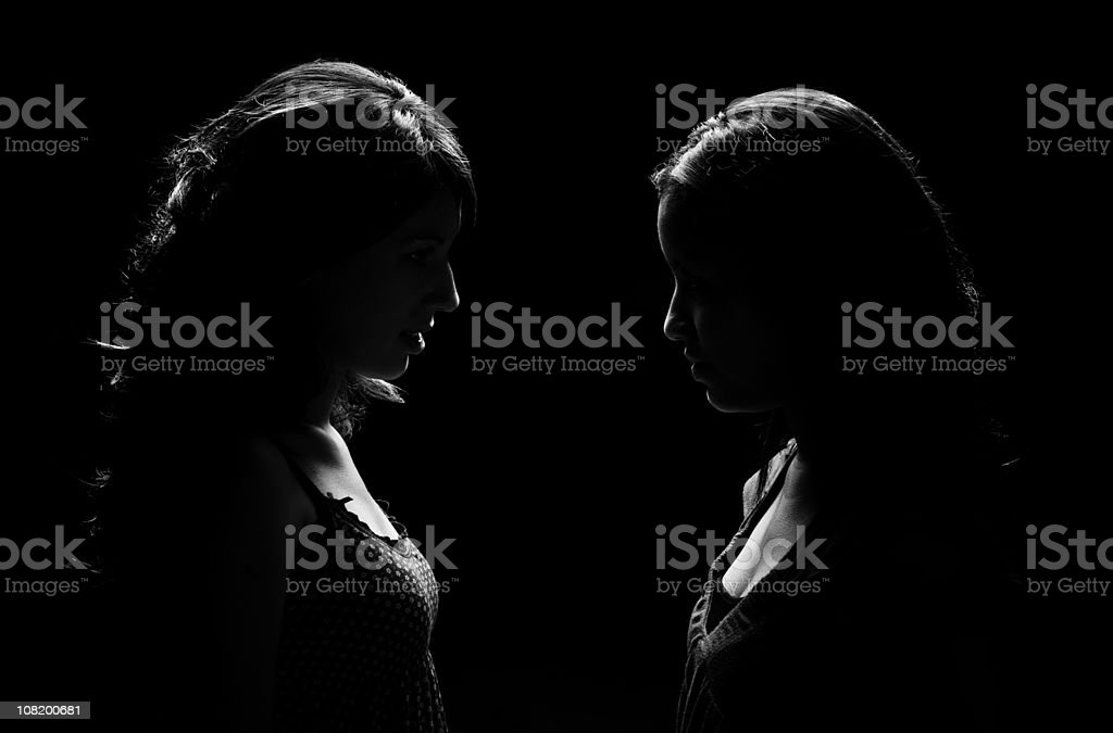 Low Key Lit Portrait of Two Woman Facing Each Other stock photo