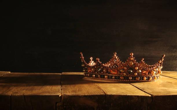 low key of beautiful queen/king crown over wooden table. vintage filtered. fantasy medieval period - tron zdjęcia i obrazy z banku zdjęć