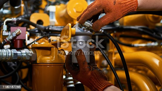Low key photo of hydraulic pipes maintenance on heavy industry machine in a garage.