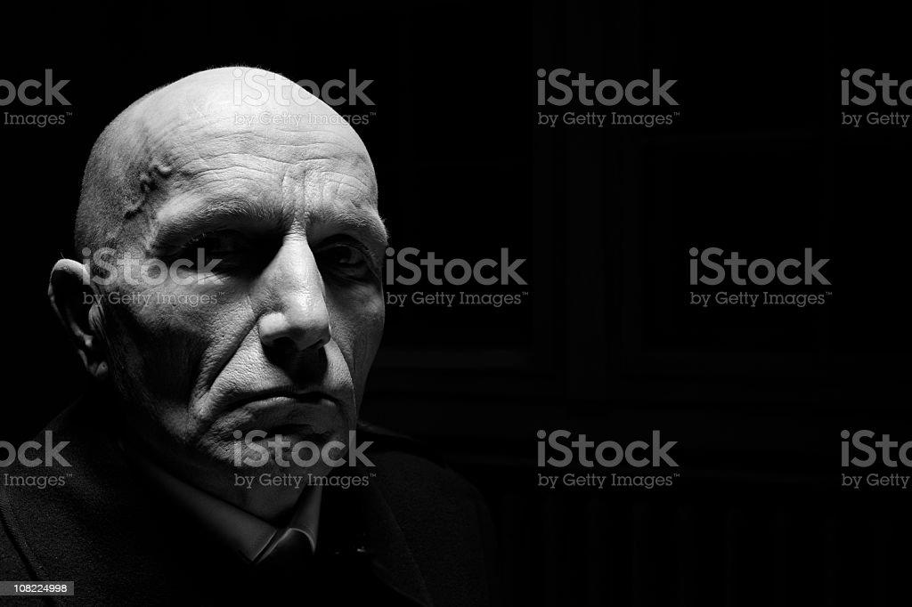 Low Key Potrait of Bald Senior Man in the Dark stock photo