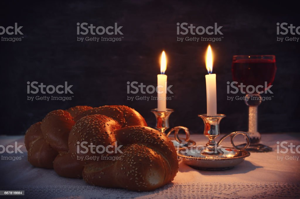 Low key shabbat image. challah bread, shabbat wine and candles stock photo