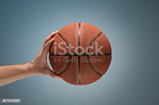 Low key shot of a hand holding a basket ball at studio