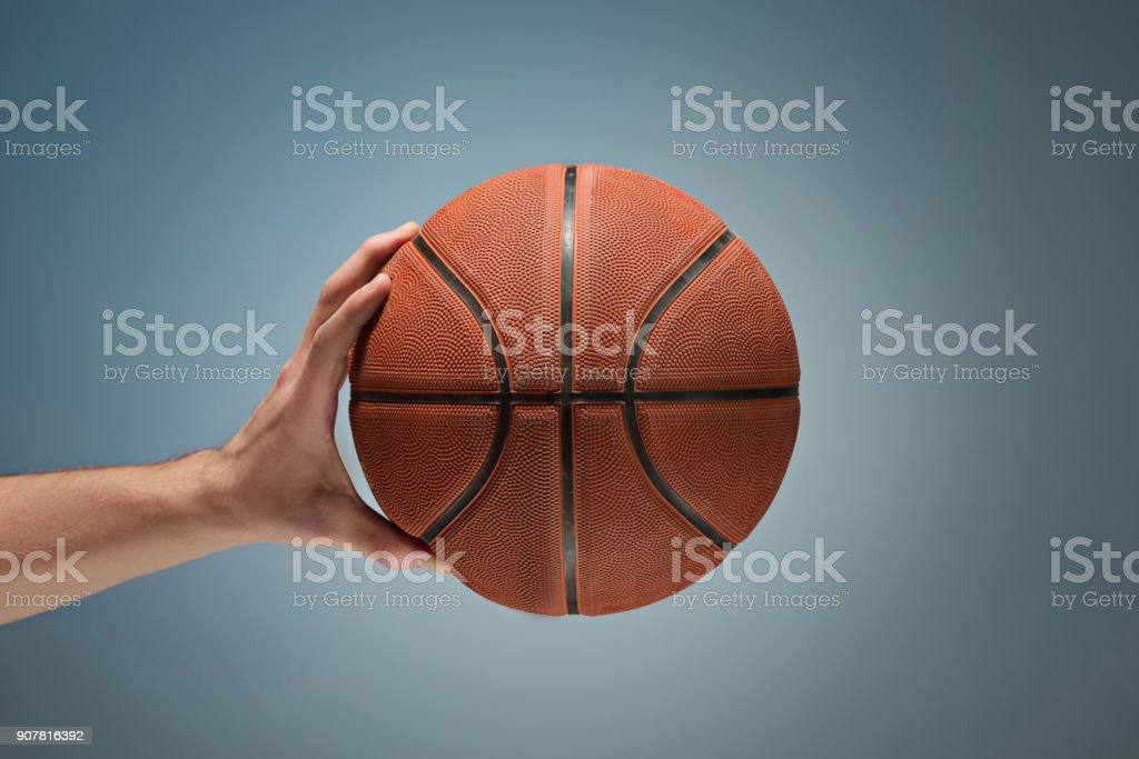 Low key shot of a hand holding a basket ball stock photo