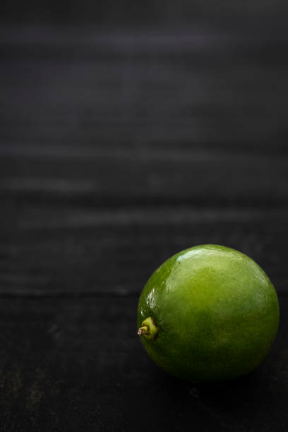 Low Key Shot of a Single Lime with Copy Space stock photo
