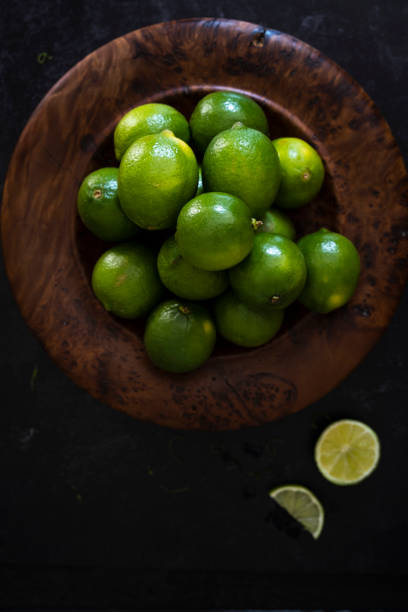Low Key Shot of Limes in a Wooden Bowl stock photo