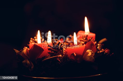 istock Low light Christmas Advent wreath with burning red candles on black background 1044340510