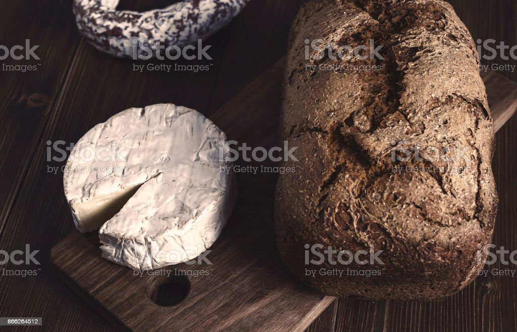Low lite color graded image of white mold cheese, sausige and whole grain bread stock photo