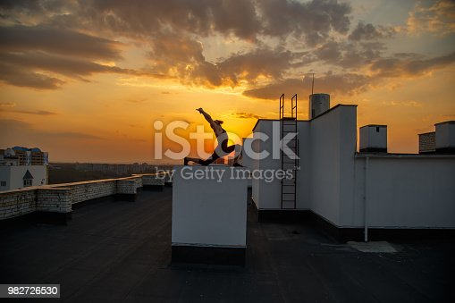 A middle-aged man is engaged in yoga on the roof. Yoga on the roof at sunset.