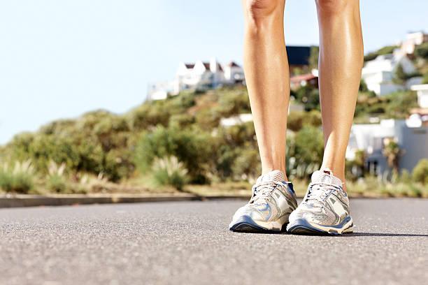 niedrige abschnitt einer frau trägt sport schuhe im freien - bein tag routine stock-fotos und bilder