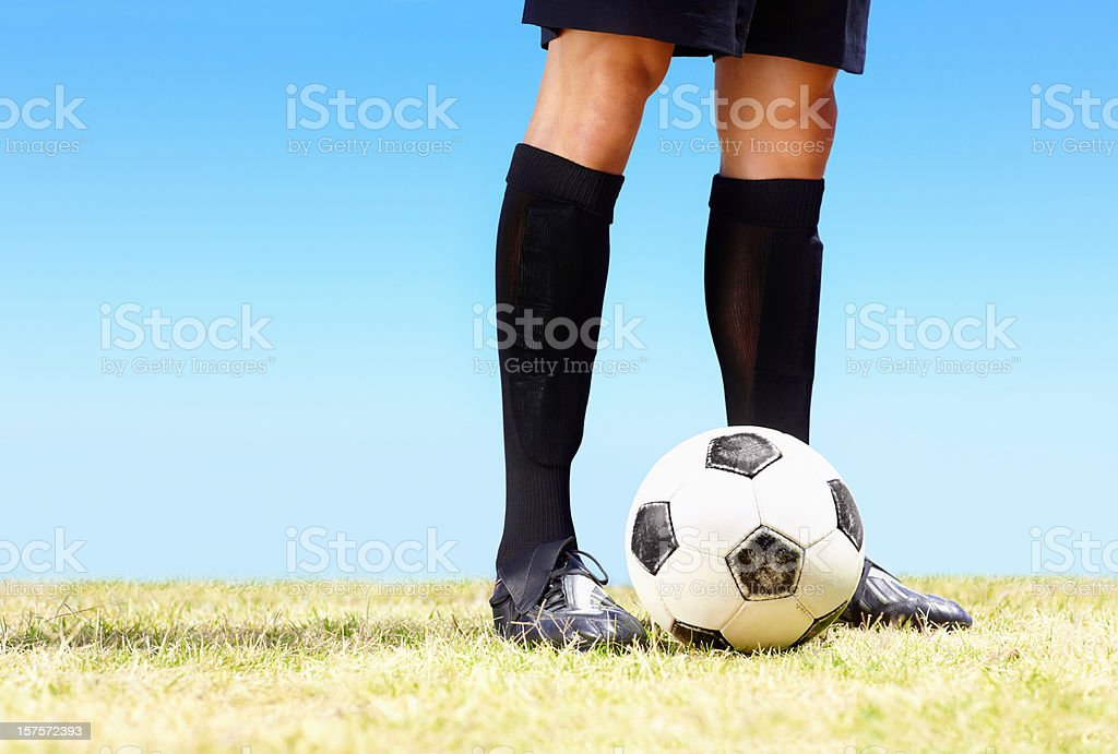 Low section of a footballer with football on field royalty-free stock photo