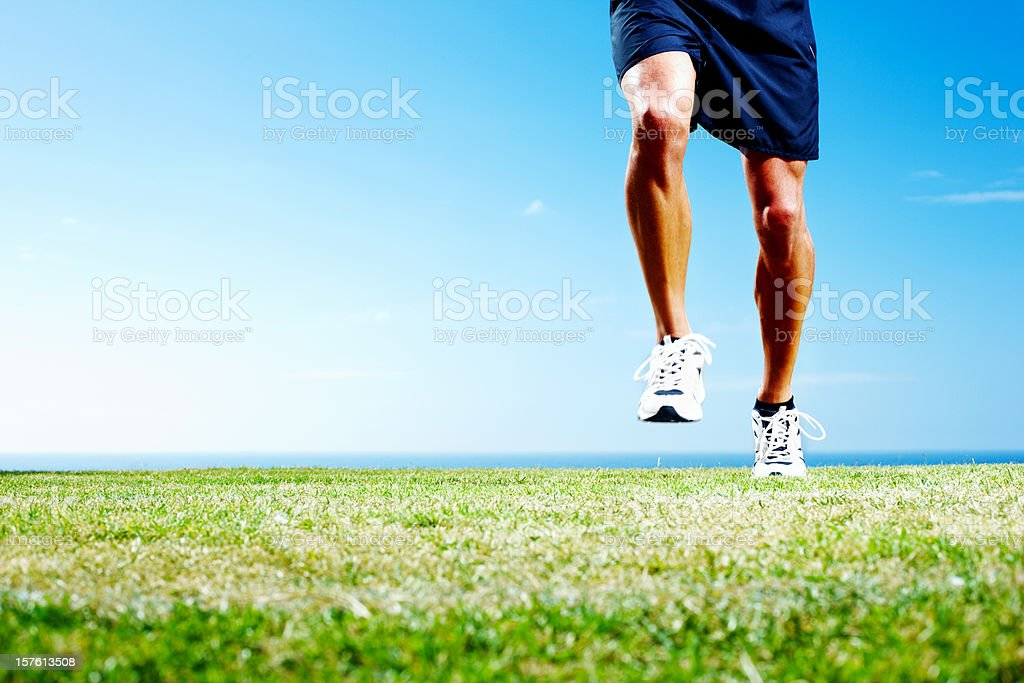 Low section of an athlete jogging on field royalty-free stock photo