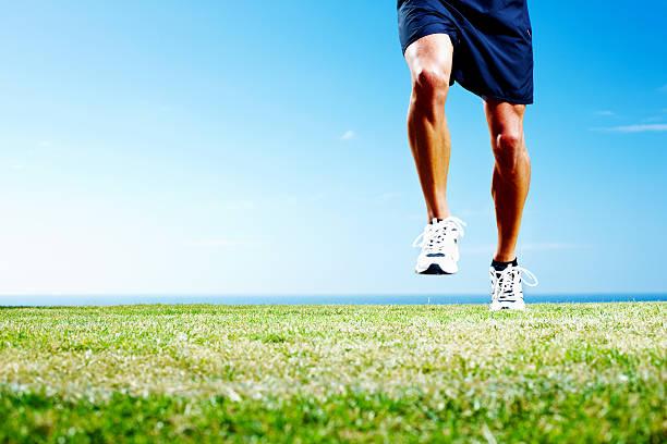 niedrige abschnitt einer sportler joggen auf dem feld - bein tag routine stock-fotos und bilder