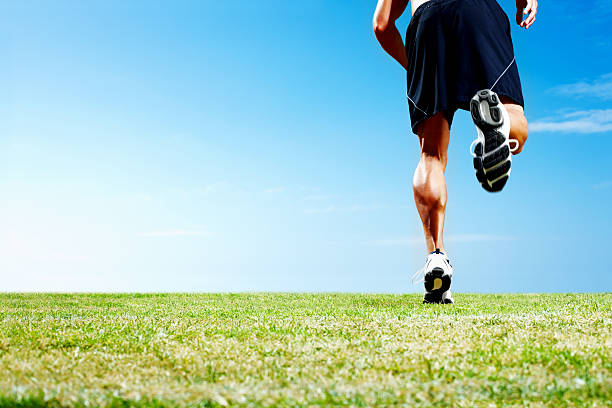 niedrige abschnitt einer dynamischen athlet läuft über feld - bein tag routine stock-fotos und bilder