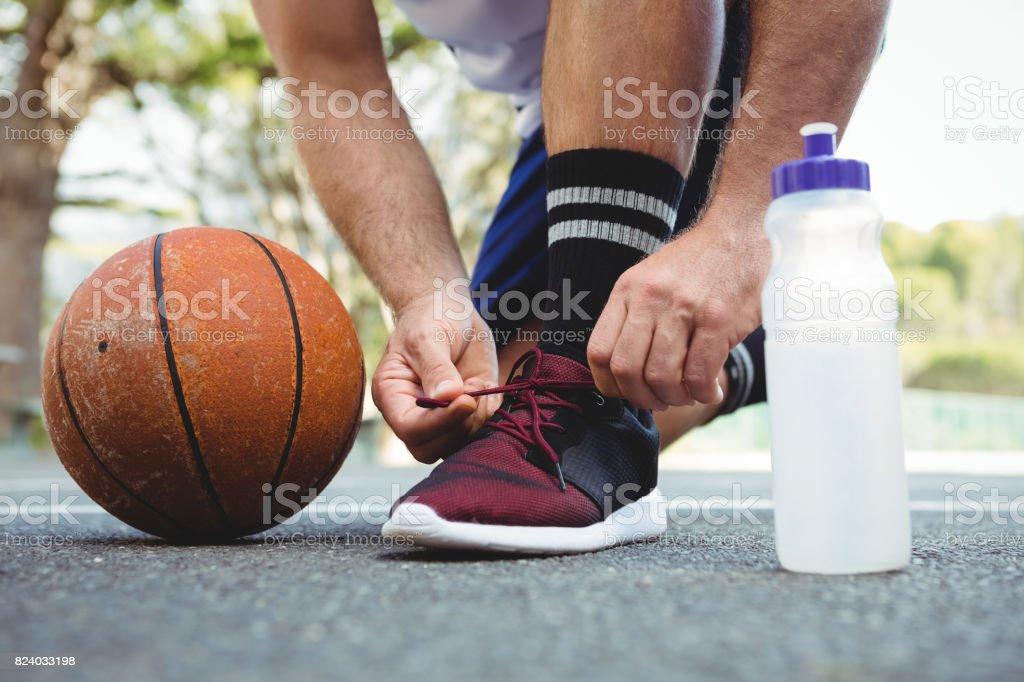 Low section of basketball player tying shoelace stock photo